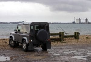 Land Rover Defender sitting on the water's edge